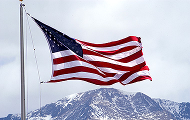 image of an American flag with Pikes Peak in the background